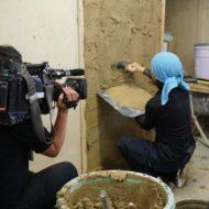 塗り壁トレーニングの模様 中央に訓練生が鏝で土壁を塗っている、左側のテレビカメラで撮影中