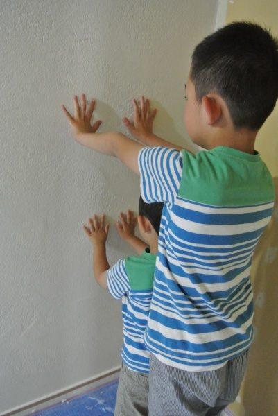 兄弟2人が漆喰の壁に向かって手を押し当てて手形を付けている
