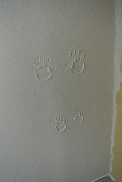 漆喰の壁に兄弟2人の手形