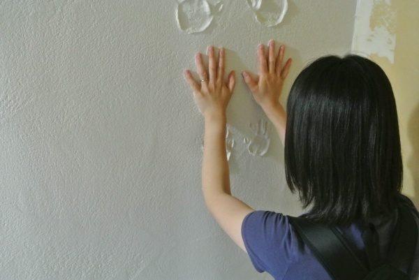 お母さんが漆喰の壁に向かって手形を付けている