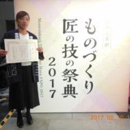 ものづくり匠の技の祭典2017の看板の前で表彰状を持つ福吉奈津子