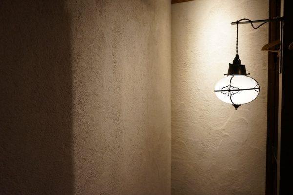 飲食店に施工した原田左官オリジナル素材「空 - KUU」の壁と横に照明器具