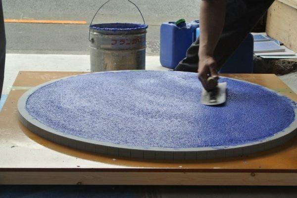 円形天板に青色ビールストーン塗りつけ中