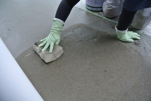 床のモルタル施工セメントをスポンジでふき取っている