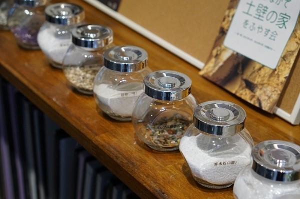 サカンライブラリー画像9 瓶入りの砂や土などの素材サンプルが並んでいる 寒水石3厘 白色 ミックス磨き石 様々な色 珪砂7号 白色 その他左官素材5種類ほど 後ろにはたてかけた冊子