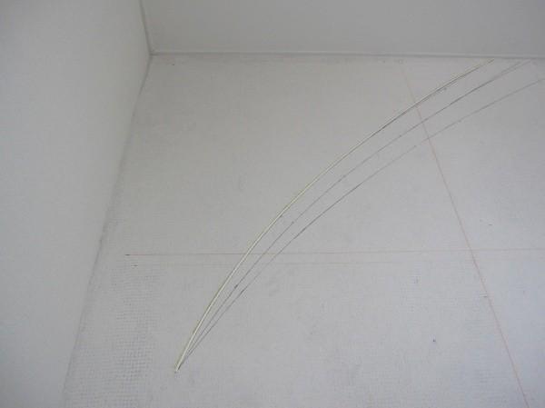 デザイン図の線に従い壁に原棒を貼り付けている
