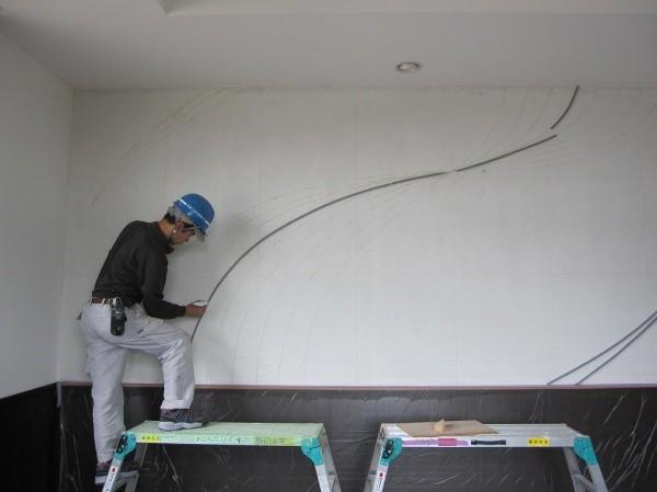 職人さんが壁にフェルトの原棒を貼り付けている