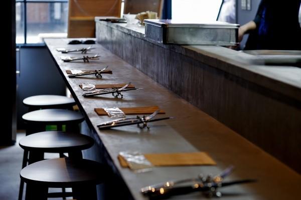 飲食店のカウンターにブラウンのモールテックス。フォークと箸が並んでいて椅子がある