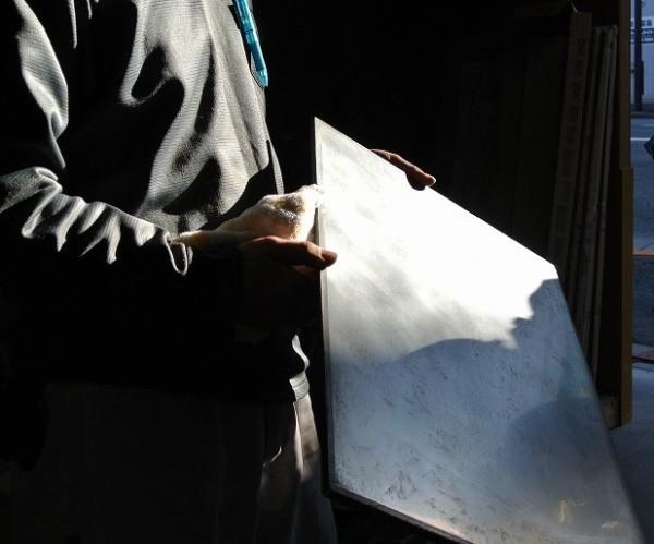 ミダスメタル亜鉛の見本板を持って光が反射している状態