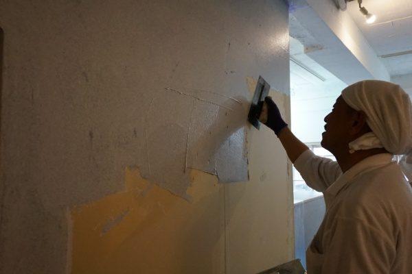 壁に左官職人が下塗りを行っている