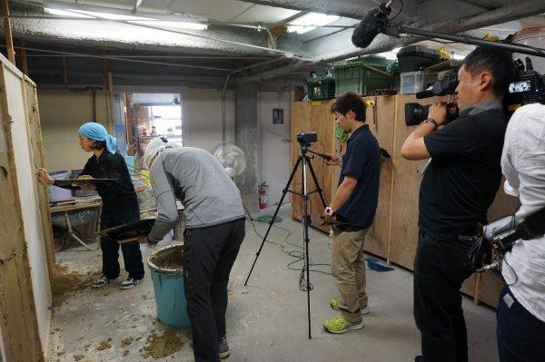 テレビ取材の模様 中央は塗り壁講師、左に訓練生2名