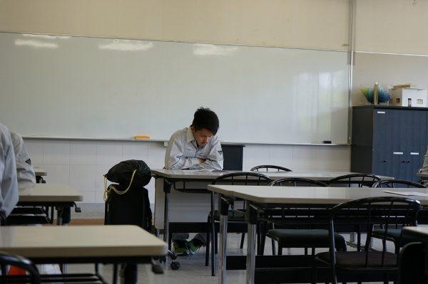 入校式で机に向かい座っている緊張した様子の石田君