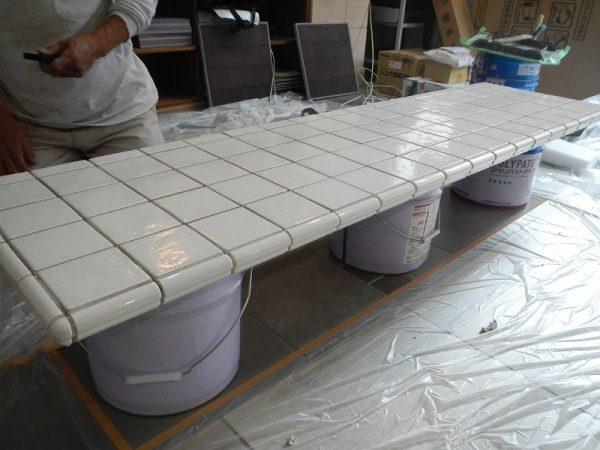 中央に白いタイル張り仕上げのテーブル