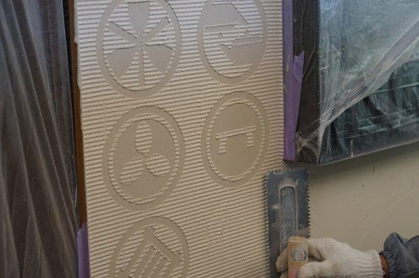 お寿司や徳利の紋が入った特殊校倉仕上げ壁施工中の様子