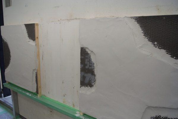 モルタルを塗り付け、型どりやカービングを行い、ギルドセメントを塗り付けた壁