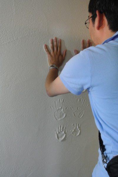 お父さんが漆喰の壁に向かって手形を付けている
