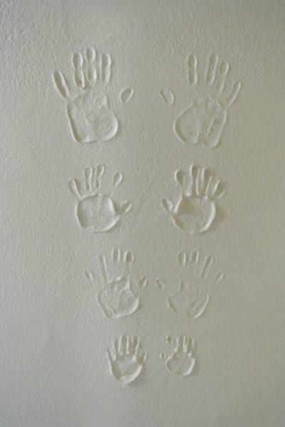 漆喰の壁に家族4人の手形