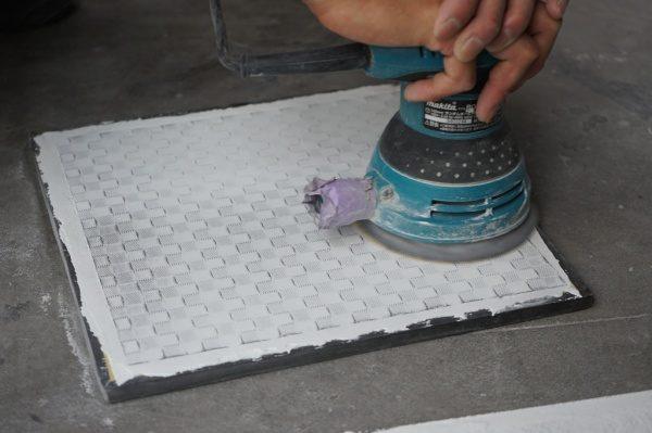 ポリーブルに埋め込んだ金属メッシュをオービットサンダーで研ぎ出します