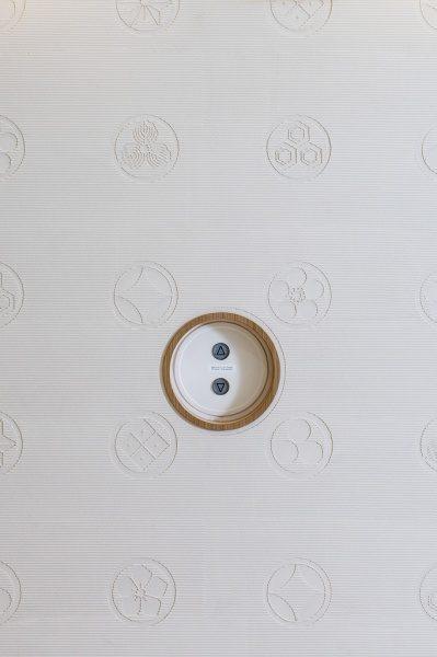 浅草ROXまつり湯エレベーターの壁の左官レリーフ、エレベーターのボタンも合わせた○デザイン