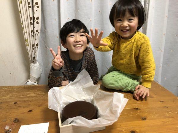 中央に社員さんの子供二人が笑顔で写っている 中央下にチョコレートケーキ