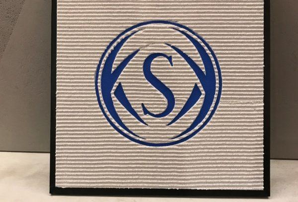左官で作成した昭和化学工業のマーク 白地に青で櫛引仕上げ