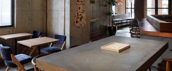 カフェのグレーのモールテックステーブルとコンクリートの内装