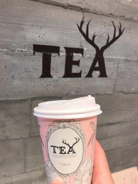 ドリンクカップと店名ロゴの入ったうづくり木目モルタルの柱