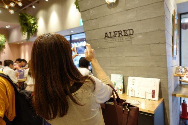 店名ロゴの入ったうづくり木目モルタルの柱を撮影している様子