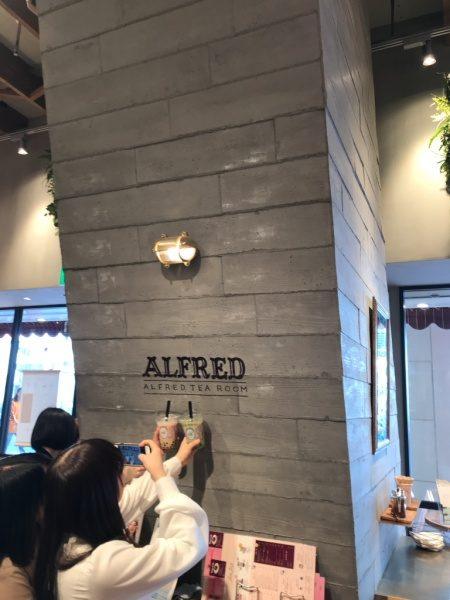 うづくりモルタル柱の前でコーヒーカップを持ちポーズをして撮影する二人の人物