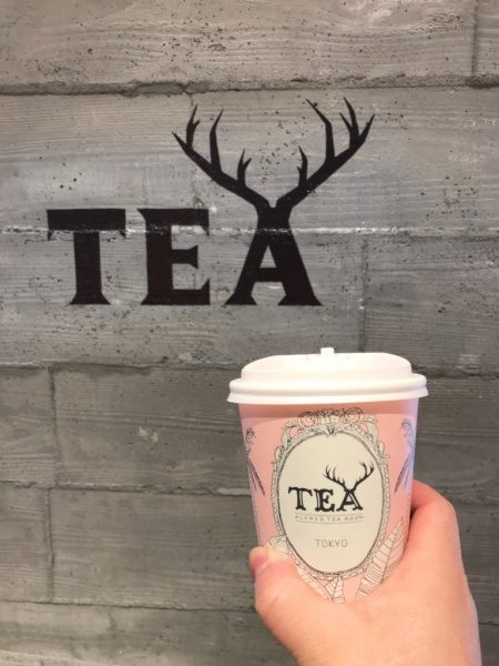 ティーカップと店名ロゴの入ったうづくり木目モルタルの柱