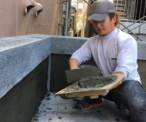 鏝板に乗せた洗い出し材料を壁面に塗りつける様子原田左官熊崎さん