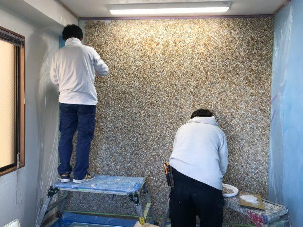 2人の人物が洗い出しネットストーンを壁に施工している様子