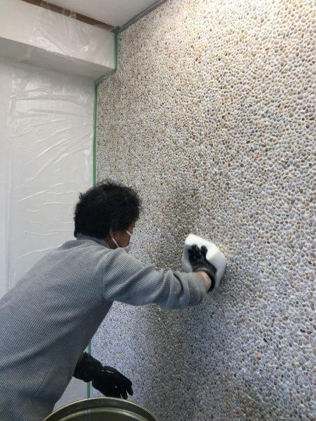 1人の人物が洗い出しネットストーン目地詰め施工後に拭き取りをする様子