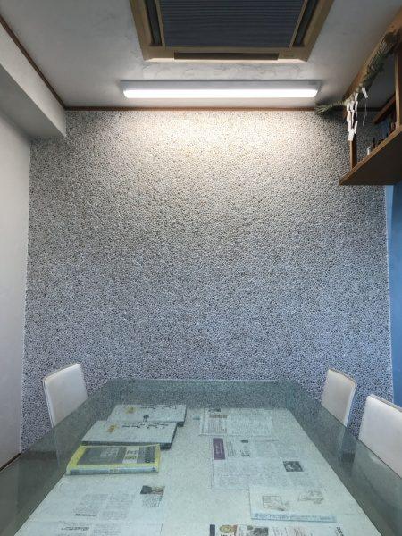 奥に洗い出しネットストーンの壁、手前にテーブルと椅子、上部に神棚と空調と照明