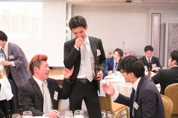 年明け披露会で3人の男性が談笑する様子