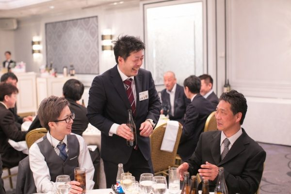 年明け披露会で飲み物などを手に持ち3人の男性が談笑する様子