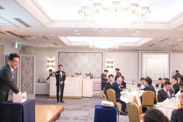 年明け披露会の大抽選会でクジを選ぶ男性とテーブルから眺める社員さん達