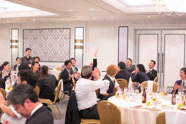 年明け披露会の大抽選会で手を挙げる男性と拍手を贈る社員さん達