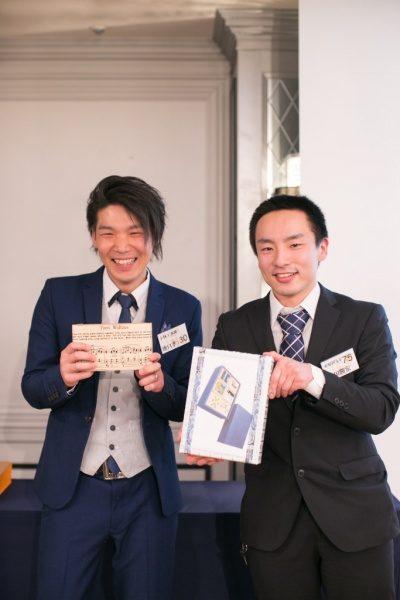 年明け披露会の大抽選会で当選した物をカメラに見せている笑顔の男性二人