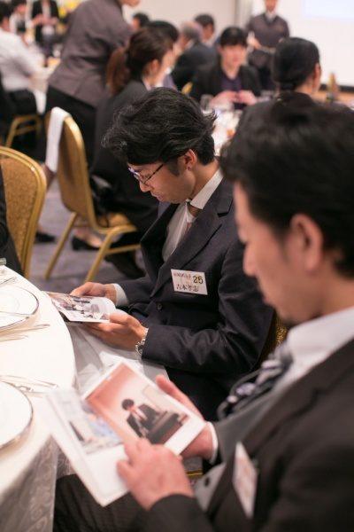 年明けフォトブックを読んでいる2人の男性と奥にはテーブル席に座る男性と女性