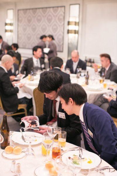 年明けフォトブックを読んでいる男性とそれを覗き込んでいる男性、奥にはテーブル席に座っている男性達