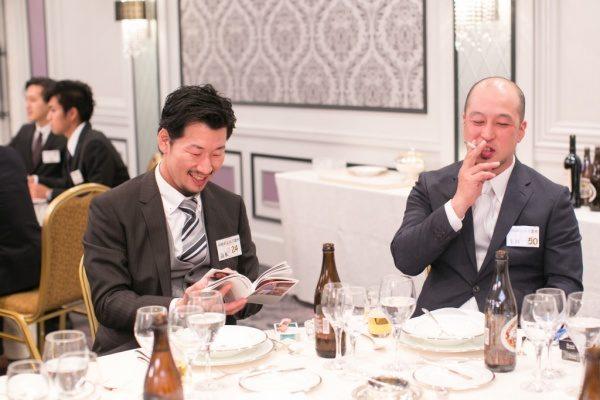 笑顔でフォトブックを読んでいる男性と笑顔でタバコを吸っている男性、左奥には他のテーブル席の男性達