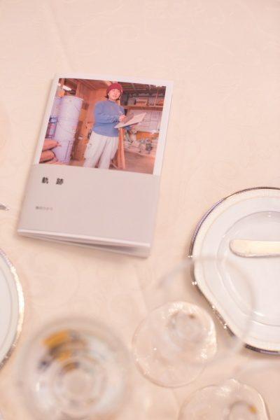 テーブルに乗っている年明けフォトブックの表紙とお皿とグラス