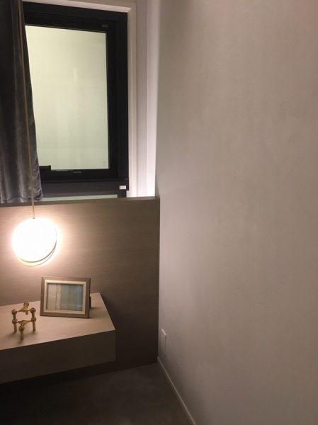 白色のオルトレマテリアのフィーネ仕上げの壁のある室内、小物が2つあり照明や出窓とカーテンがある
