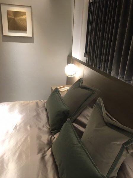 白色のオルトレマテリアのフィーネ仕上げの壁、鏝模様仕上げ、手前にベッドと枕、左上に絵画、右上にカーテン、真ん中に照明がある