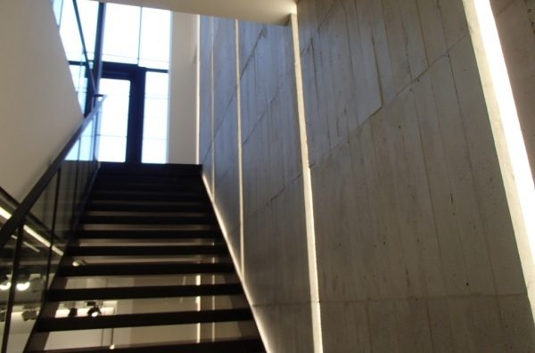 浮造り木目モルタルで施工したアパレルショップの壁、壁は縦の芋張りで色はモルタル素地色