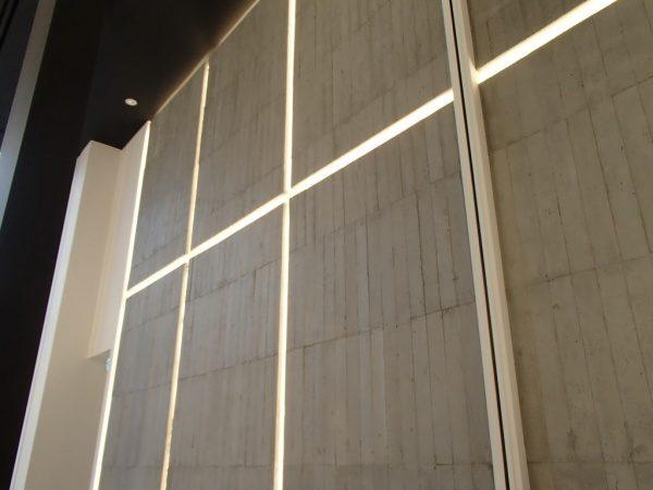 浮造り木目モルタルで施工したアパレルショップの壁、壁は縦の芋張りで色はモルタル素地色、右からのアングル