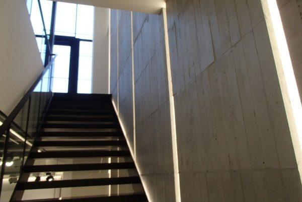 浮造り木目モルタルで施工したアパレルショップの壁、壁は縦の芋張りで色はモルタル素地色、階段がある