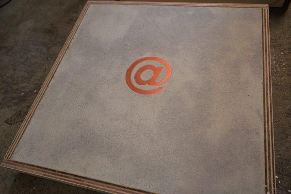 アットマークの形をした真鍮入りモルタル象嵌仕上げサンプル