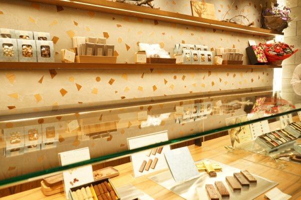 木片入りのモラート仕上げの壁、棚にはチョコレートショップの商品が並んでいる、手前側にガラスのカウンターの中にも商品がある